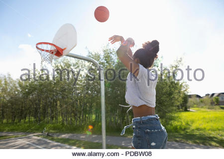 Young woman playing basketball at park basketball court - Stock Photo
