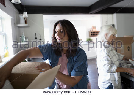Daughter helping senior mother downsize, packing kitchen - Stock Photo