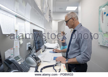 Male doctor using computer in clinic - Stock Photo