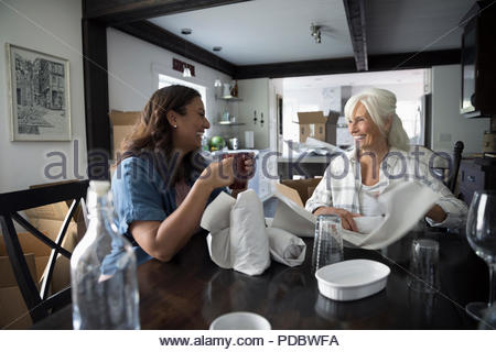Daughter helping senior mother downsize, packing dishes - Stock Photo