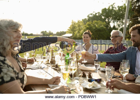 Friends drinking champagne and wine at sunny garden party patio table - Stock Photo