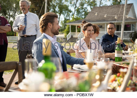 Friends Enjoying Wedding Reception Lunch At Rural Table Stock Photo
