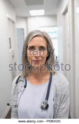 Portrait confident female doctor in clinic corridor - Stock Photo