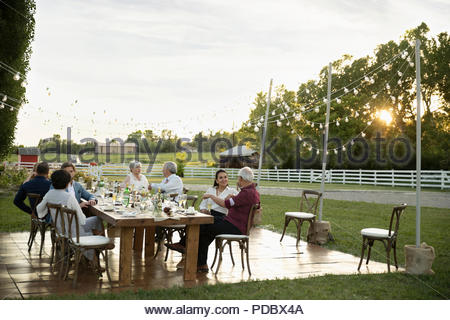 Friends talking and drinking champagne at wedding reception table in rural garden - Stock Photo