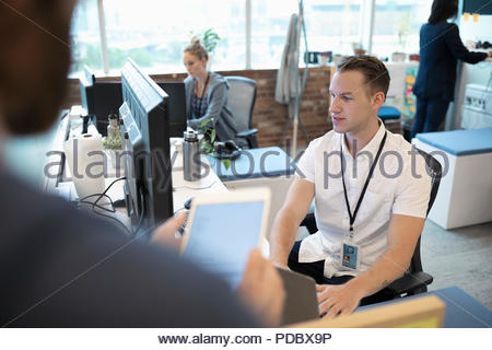 Businessman at computer talking with colleague in office - Stock Photo