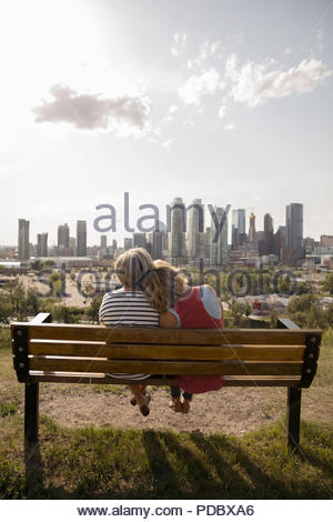 Affectionate mother and daughter on park bench overlooking sunny city - Stock Photo