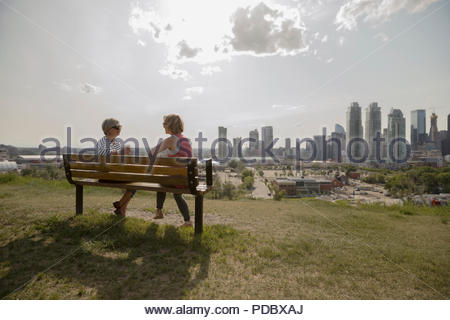 Mother and daughter talking on bench in sunny urban park - Stock Photo