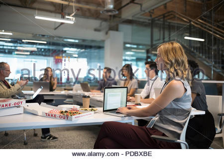Focused businesswoman using laptop in pizza lunch office meeting - Stock Photo