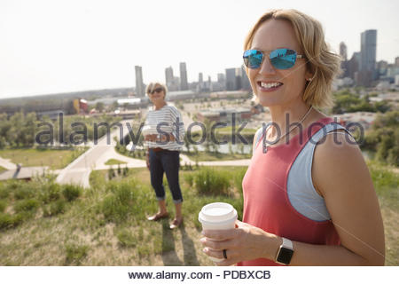 Portrait smiling woman drinking coffee and walking in sunny urban park with mother - Stock Photo