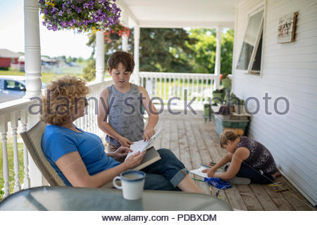 Grandson showing drawing to grandmother on porch - Stock Photo