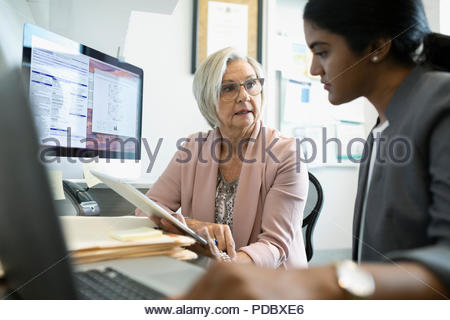 Female doctor and senior patient using digital tablet in clinic office - Stock Photo