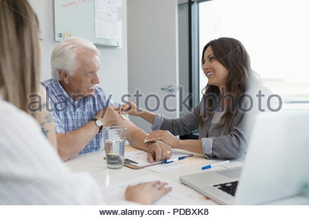 Female doctor applying smoking patch to arm of senior male patient in clinic office - Stock Photo