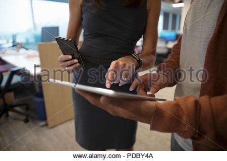 Close up businessman and businesswoman using digital tablet and smart phone in office - Stock Photo