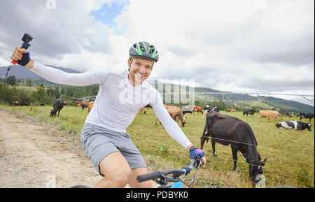 Portrait carefree man with wearable camera mountain biking on dirt road along cow pasture - Stock Photo