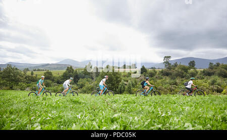 Friends mountain biking in idyllic, remote field - Stock Photo