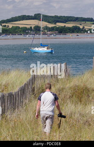 Nature Photographer Strolling over Dawlish Warren Nature Reserve, Looking towards the Exe Estuary and Rolling Devon Farmland. Summer, UK. - Stock Photo