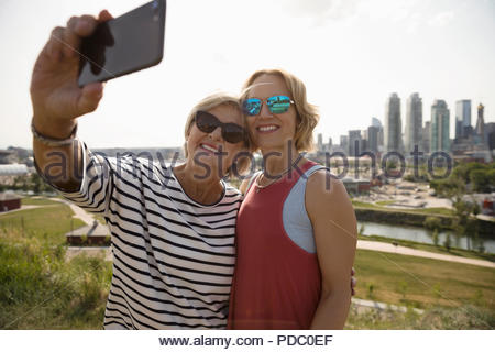 Smiling mother and daughter taking selfie in sunny urban park - Stock Photo