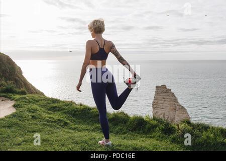 athletic girl in stylish sportswear stretching leg on cliff near sea, Etretat, France - Stock Photo