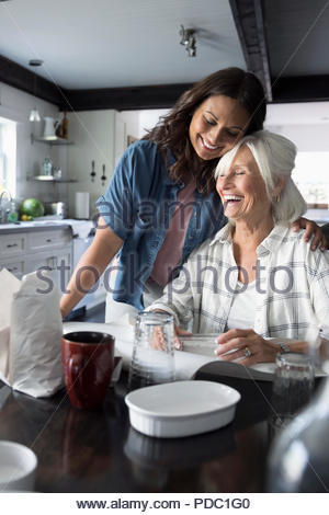 Affectionate daughter helping senior mother downsize, packing dishes - Stock Photo