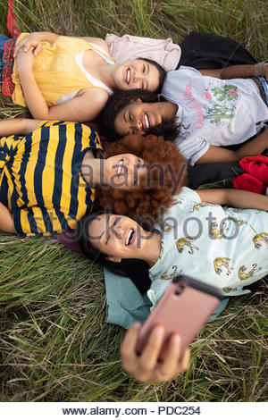 Overhead view teenage girl friends laying in tall grass, taking selfie - Stock Photo