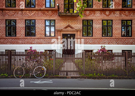 front view of parked bicycle near wooden fence in front of building in Copenhagen, Denmark - Stock Photo