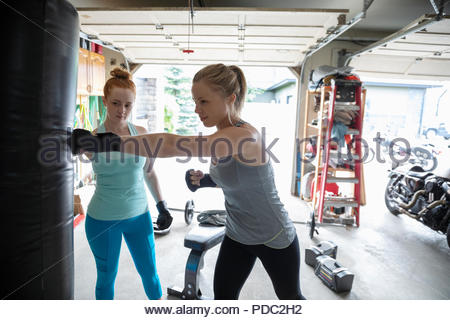 Young women friends boxing at punching bag in garage - Stock Photo