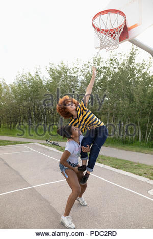 Teenage girl friends reaching for net on park basketball court - Stock Photo