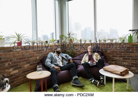 Creative businessmen napping on beanbags in office - Stock Photo
