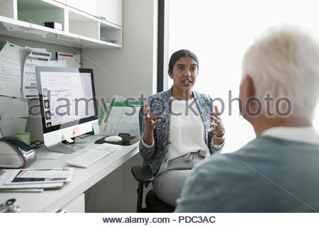 Female doctor talking with senior male patient in clinic office - Stock Photo