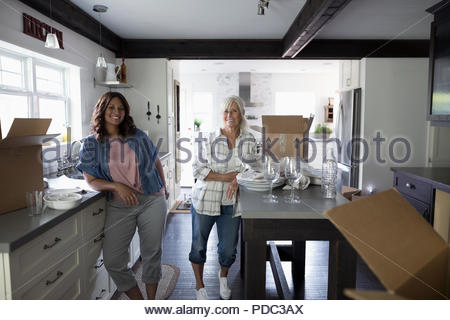 Portrait smiling daughter helping senior mother downsize, packing dishes in kitchen - Stock Photo