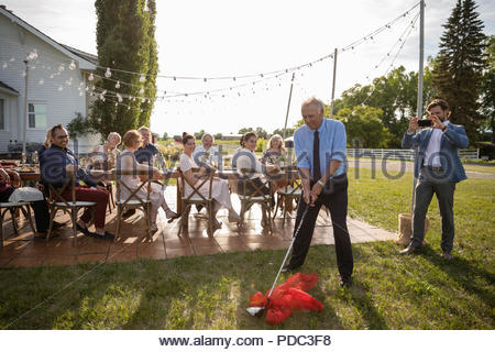 Son with camera phone photographing father with golf club gift at retirement party in rural garden with friends - Stock Photo