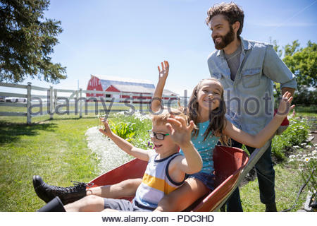 Playful father pushing daughter and son in wheelbarrow in sunny rural garden - Stock Photo