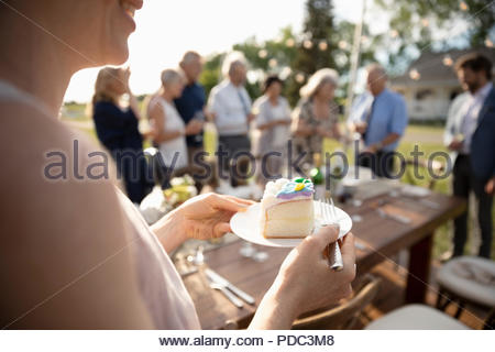 Woman eating cake, celebrating at sunny garden party with friends - Stock Photo