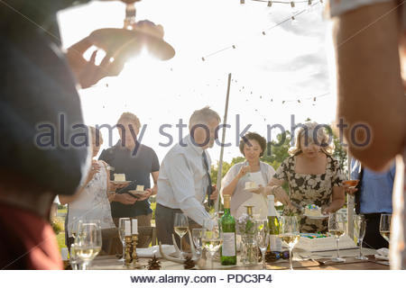 Friends celebrating, enjoying cake at sunny patio table - Stock Photo