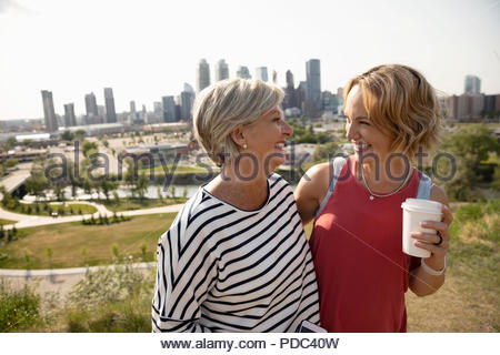Happy mother and daughter with coffee talking in sunny urban park - Stock Photo
