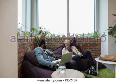 Creative businessmen using digital tablet and laptop on beanbags in office - Stock Photo
