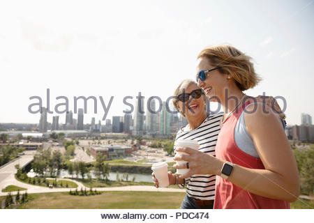Smiling mother and daughter walking in sunny urban park with coffee - Stock Photo
