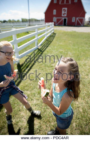 Playful sisters eating watermelon on sunny rural farm - Stock Photo