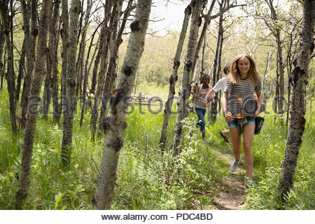 Tween girl friends running in sunny woods - Stock Photo