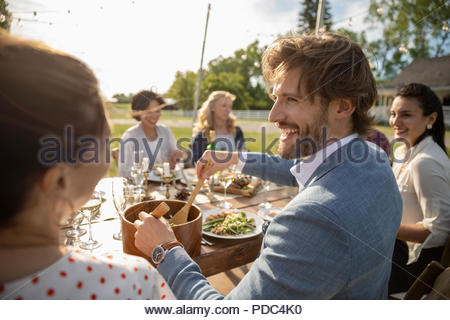 Smiling Man Enjoying Wedding Reception Lunch At Patio Table Stock