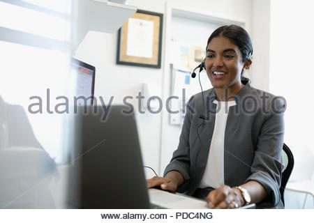 Smiling female doctor using hands-free telephone at laptop in clinic office - Stock Photo