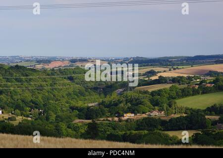 Rolling Patchwork Landscape of Wooded Devon Farmland and National Grid Pylon, looking towards Exmouth. Whitestone, Exeter, UK. August, 2018. - Stock Photo