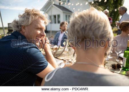 Smiling Man Enjoying Wedding Reception Lunch At Patio Table Stock