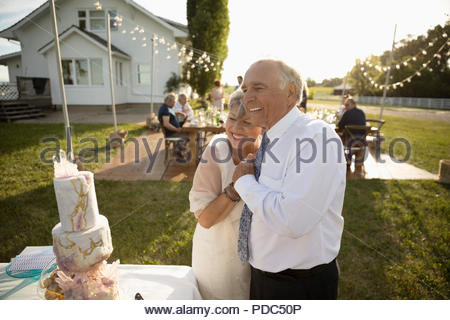 Affectionate, happy senior bride and groom hugging at wedding cake in sunny rural garden - Stock Photo