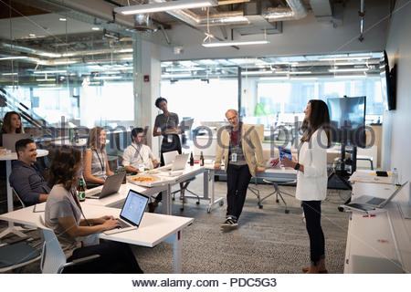 Businesswoman leading meeting in open plan office - Stock Photo