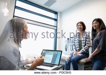 Female doctor with laptop talking with mother and daughter patient in clinic exam room - Stock Photo