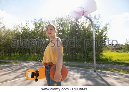 Confident, cool teenage girl with skateboard and basketball on sunny park basketball court - Stock Photo