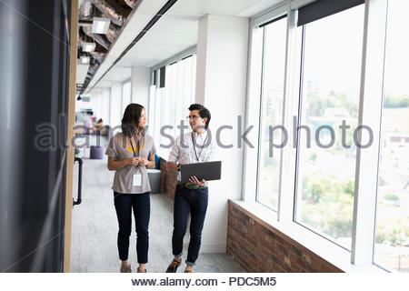 Businessman and businesswoman with laptop walking in office corridor - Stock Photo