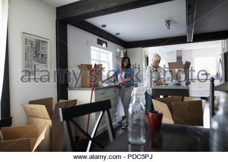 Daughter helping senior mother downsize, packing dishes in kitchen - Stock Photo