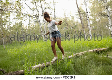Young woman balancing, walking on fallen log in woods - Stock Photo